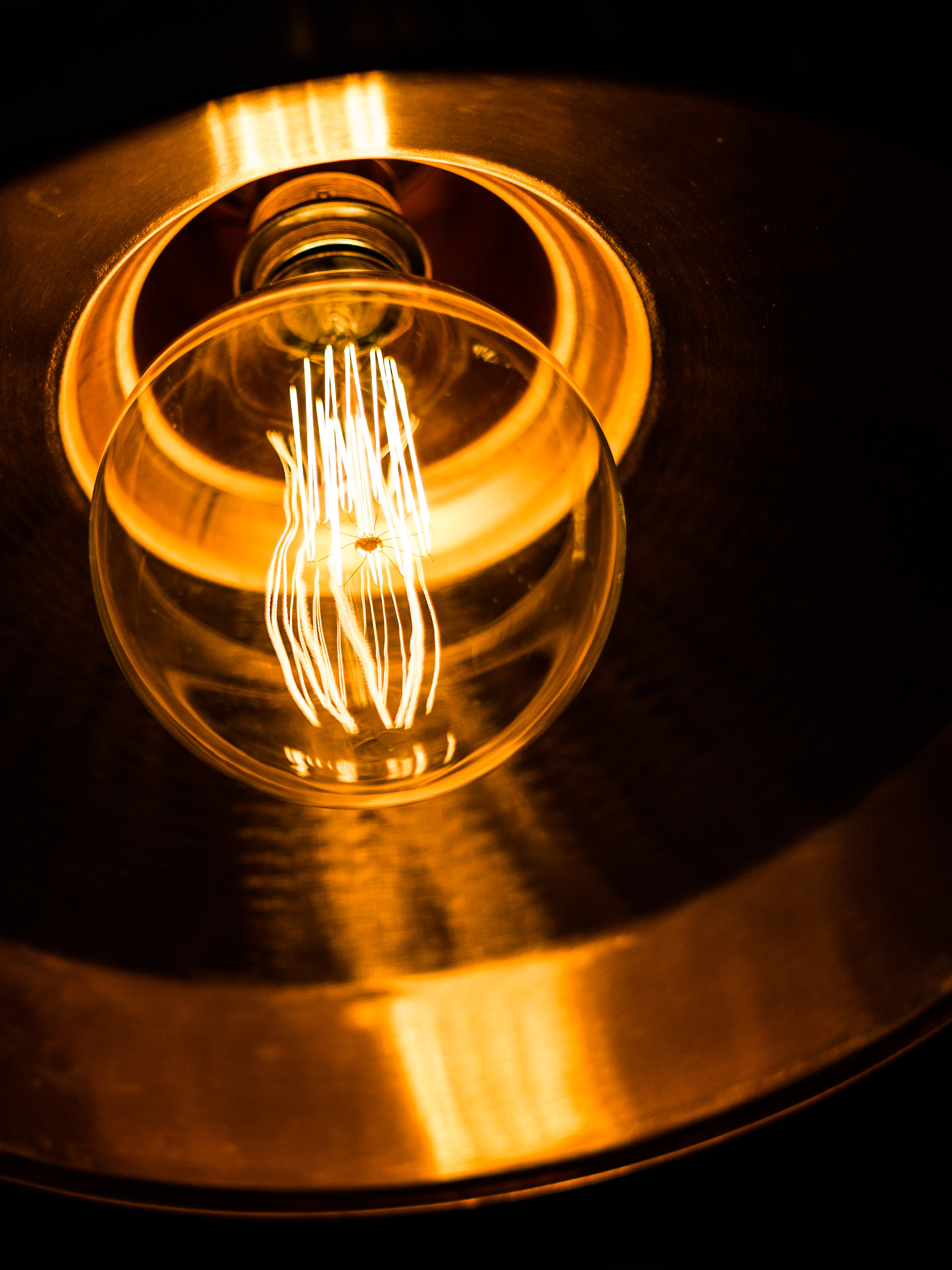 A dimly lit large globe traditional filament lamp in a copper shade