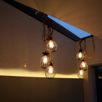 Highbury House extension lit by filament bulbs with bulb guards