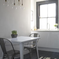 Small dining room with overhead bare bulb pendants