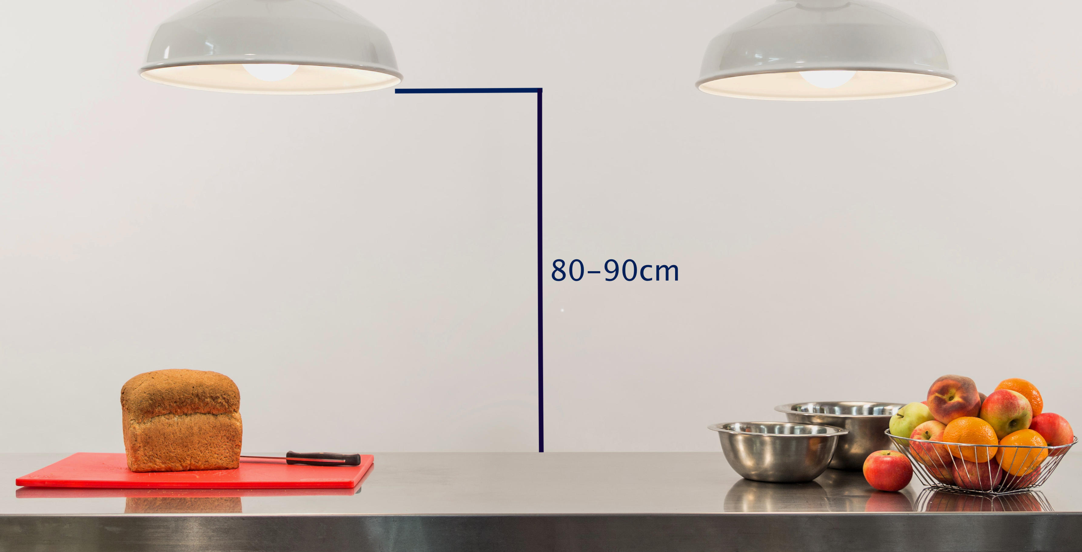 A pair of pendants lighting a kitchen island. A graphic indicates the advised height for such fixtures is between 80-90cm above the island surface.